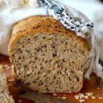 A loaf of the multigrain flaxseed bread that's been sliced open to reveal the seeds and grains on the inside