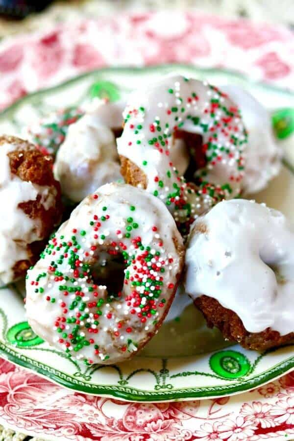 Closeup of lemon glazed gingerbread donuts with red and green sprinkles piled on a green and white plate.