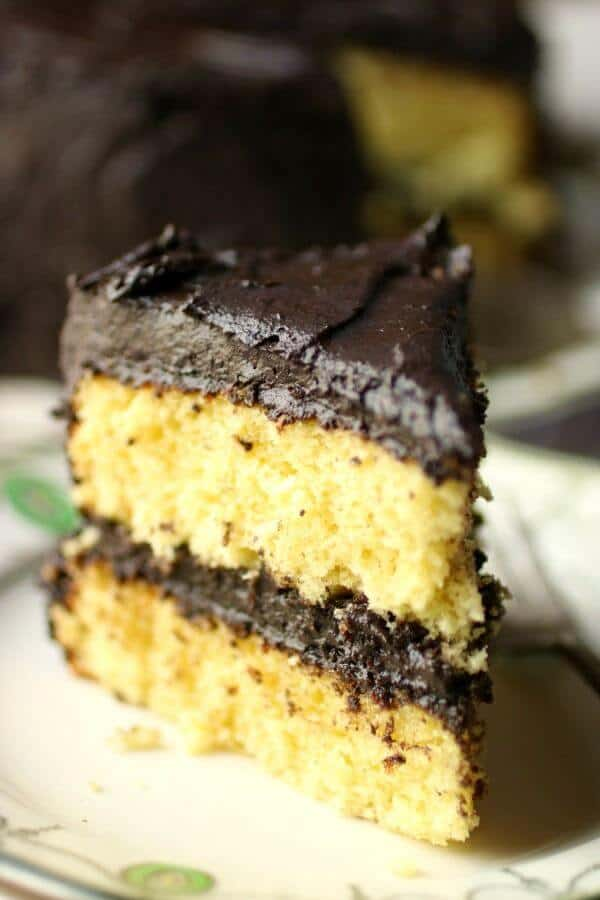 Close up of a yellow layer cake slice with fudge frosting on the top and sides as well as between the layers.
