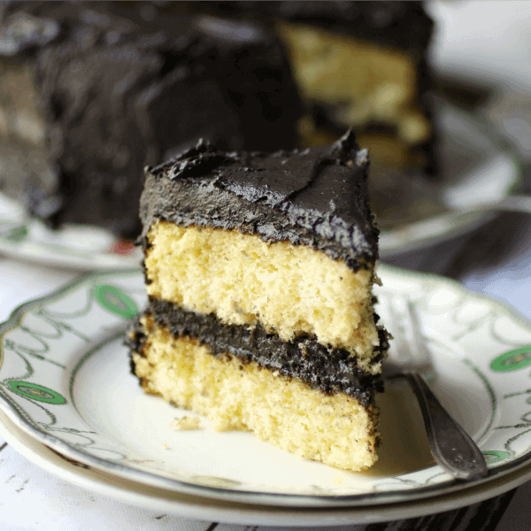 A slice of yellow layer cake with fudge frosting.