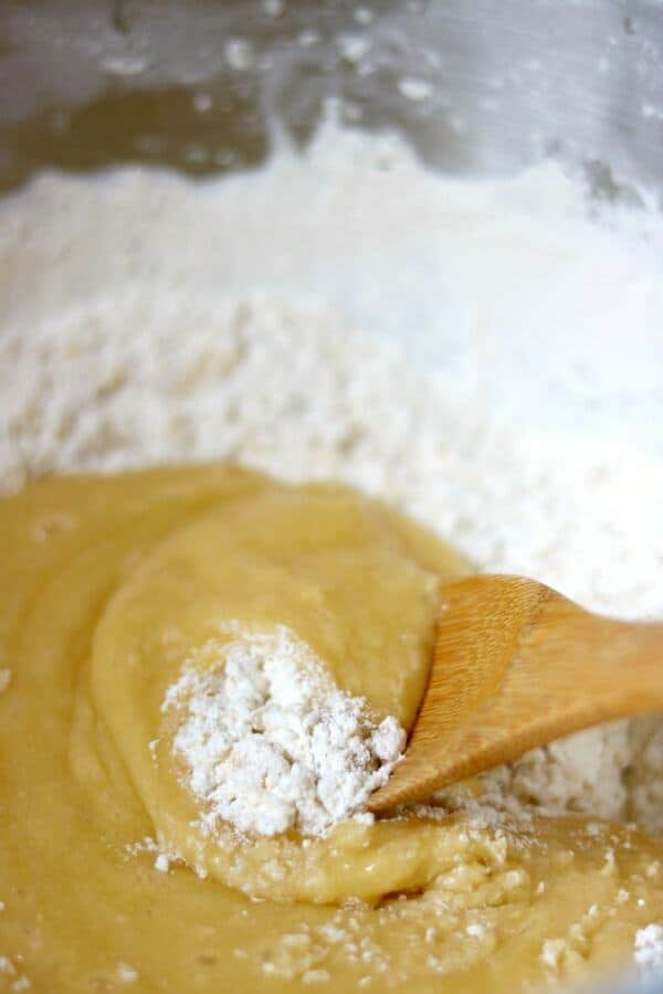 A wooden spoon stirs flour into the soft dough for best rolled sugar cookies recipe