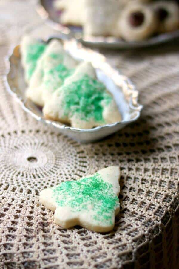 One sugar cookie is on a lace covered table while the rest of the best sugar cookies recipe with green sugar are in an antique dish