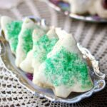 The best rolled sugar cookies ever - on an antique dish with gold trim. Cookies are cut out in Christmas tree shapes with green sugar. Recipe image