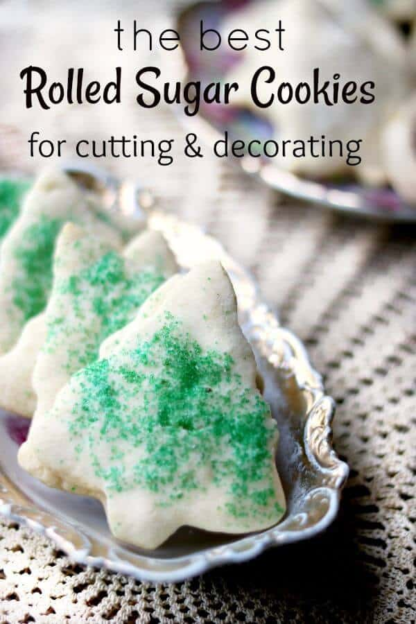 The best rolled sugar cookies! Sugar cookies cut out in Christmas tree shapes are covered in green sugar and lined up in an antique dish with gold edges. Title image