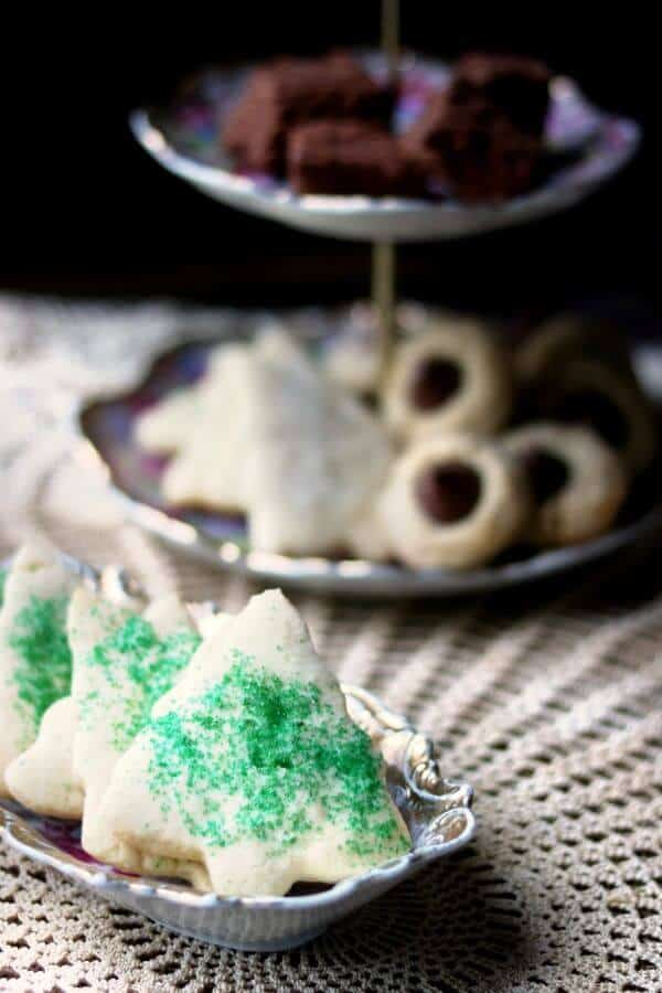 Sugar cookies sprinkled with green sugar are on a lace covered table along with an antique tiered plate of cookies. Best rolled sugar cookies recipe vertical image 4