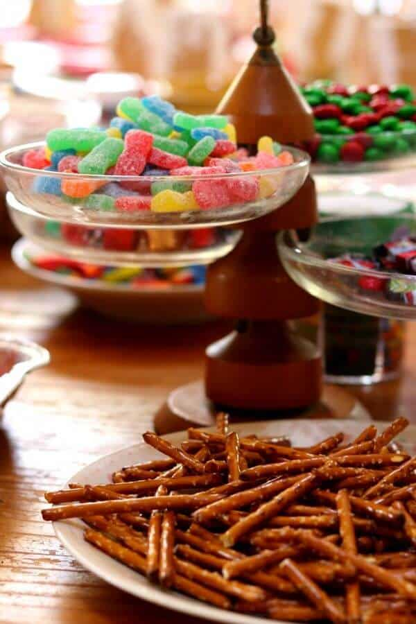 pretzels and candy on the table for the gingerbread house party