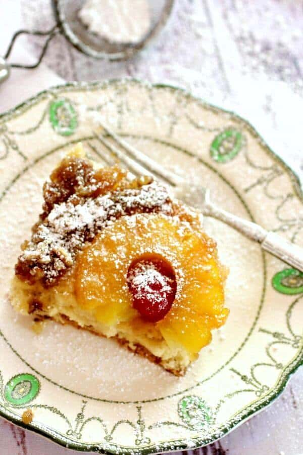 a square of pineapple upside down cake on a vintage white plate. Seen from the top the pineapple ring and cherry are clearly seen.