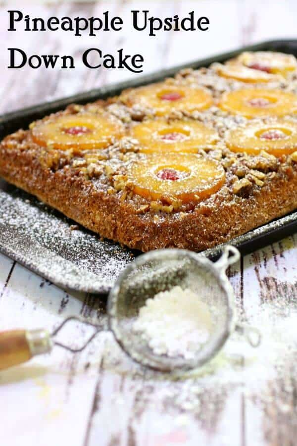 A rectangular pineapple upside down cake dusted with confectioner's sugar on a white table