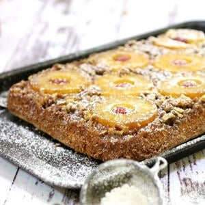 Uncut pineapple upside down cake dusted with confectioner's sugar.