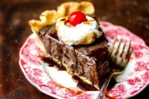 Slice of chocolate pie topped with whipped cream and a cherry, on a red transferware plate - feature image
