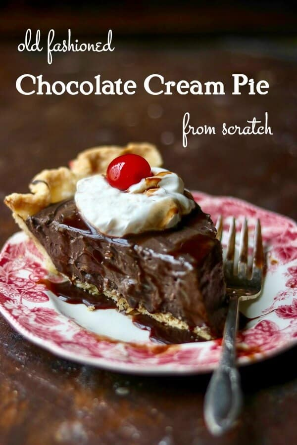 Thick slice of chocolate cream pie with whipped cream and a cherry on top. The pie is on a red transferware plate. Title image.