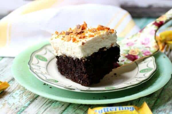 Featured image for holy cow cake - chocolate cake with whipped cream on top and chopped butterfingers candy bars sprinkled over all.