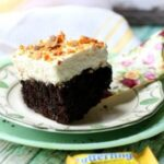 A square of chocolate holy cow cake with whipped cream topping and chopped Butterfingers candy on top. Image for recipe box