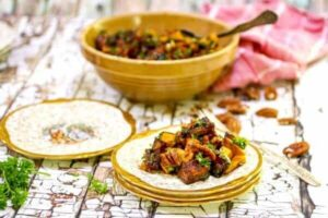 Golden sweet potatoes and pecans are diced into a salad and served on gold edged plates.