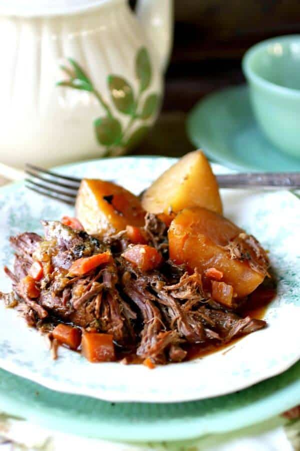 Perfect pot roast with au jus, potatoes, and carrots are served up on a vintage white and green plate. A tea pot is in the background.