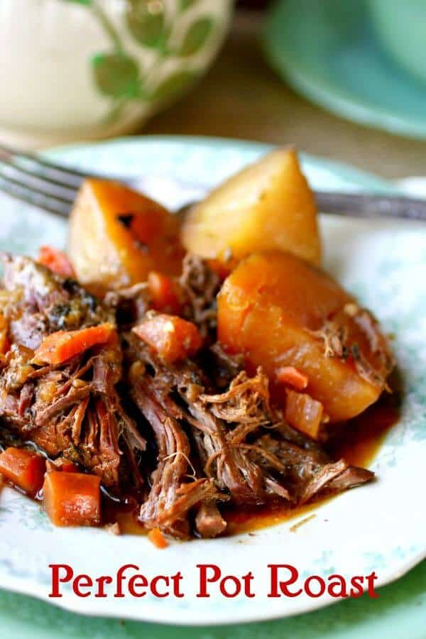 Pieces of tender, perfect pot roast, carrots, and potatoes are piled onto a vintage green and white plate with a fork and some crockery in the background. Title image for post.