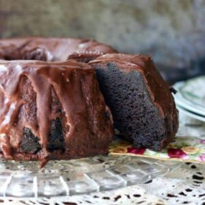 Slice of black lager chocolate cake on a flowered china cake server with a lace tablecloth underneath.