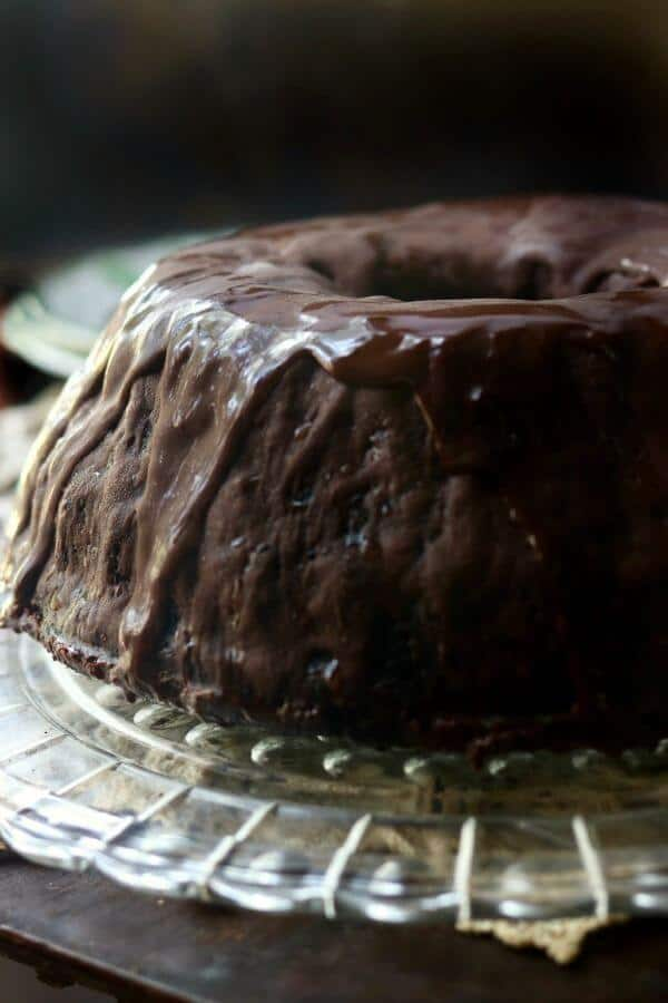 Whole black lager chocolate cake with chocolate ganache dripping down the sides