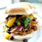 Pulled pork sandwich with mango salsa on top.