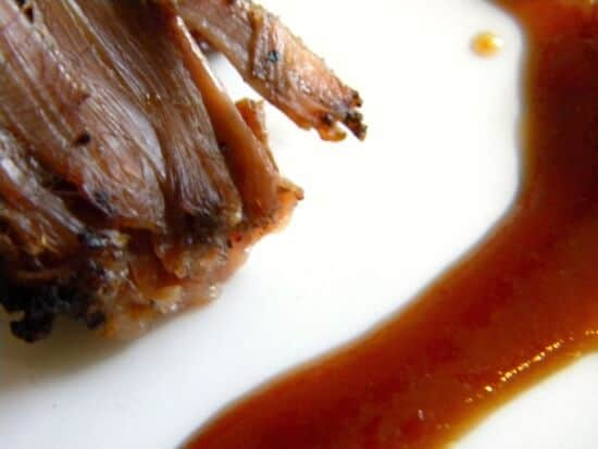 Closeup of brisket with bbq sauce on it.