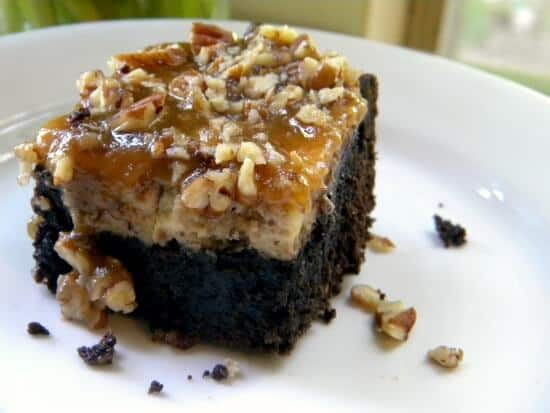 A brownie cheesecake bar on a plate with pecans tumbling off of it