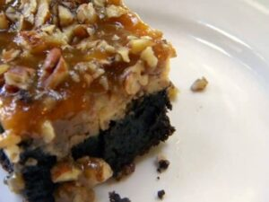 one praline cheesecake brownie. a rich brownie is covered with cheesecake then topped with pecan praline. Recipe image