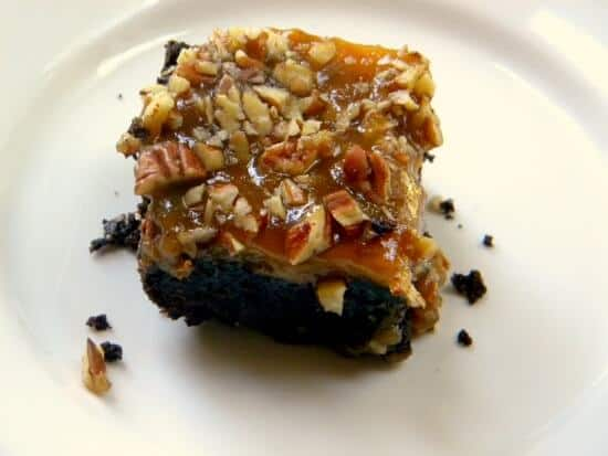 brownie cheesecake bars - a layered bar made of brownie,cheesecake, and pecan praline on a white plate