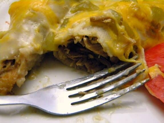 close up of creamy green chile chicken enchiladas with a fork nearby