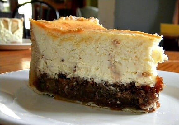 This pecan pie cheesecake has a thick layer of sweet pecan pie topped with a layer of rum and toffee cheesecake. Dense, rich, and delicious from RestlessChipotle.com