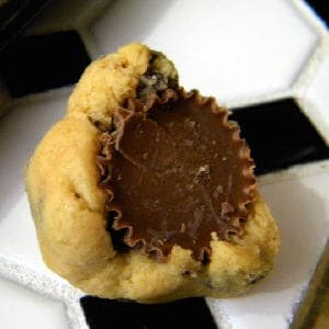 A Reeses peanut butter cup being wrapped with dough.