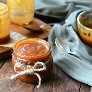 Jar of caramel sauce on a wood table.