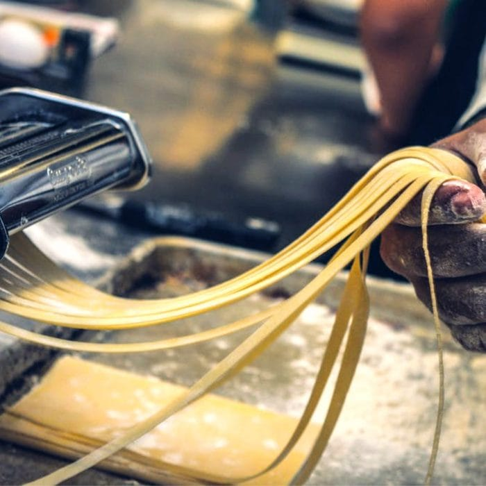 Homemade pasta being rolled by machine.