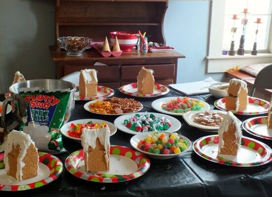 graham cracker gingerbread house party with several houses waiting to be decorated with candy