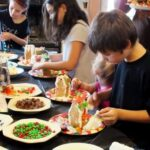 kids decorating gingerbread houses at a gingerbread house party