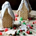 two gingerbread houses with cookies and red and green candy on a lace covered table