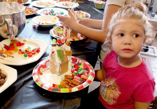 a toddler makes a house at a gingerbread house party
