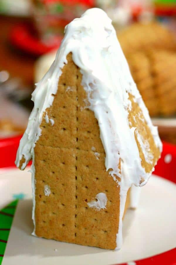 A finished gingerbread house from graham crackers is waiting to be decoraged with plenty of candy!