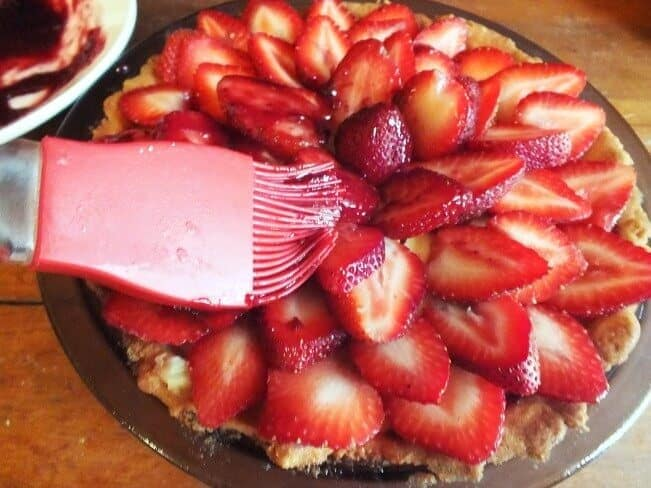 brushing on glaze to the strawberry and cream tart