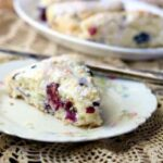 Feature image for lemon blueberry scones - a scone rests on a vintage plate with a silver knife poised and ready to add butter!