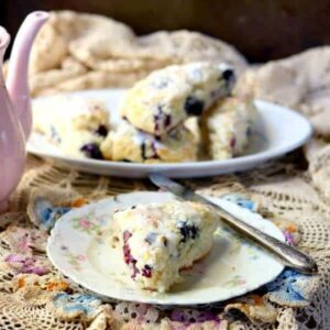 lemon blueberry scones - one rests on a plate while the rest are in the background. Square recipe image.