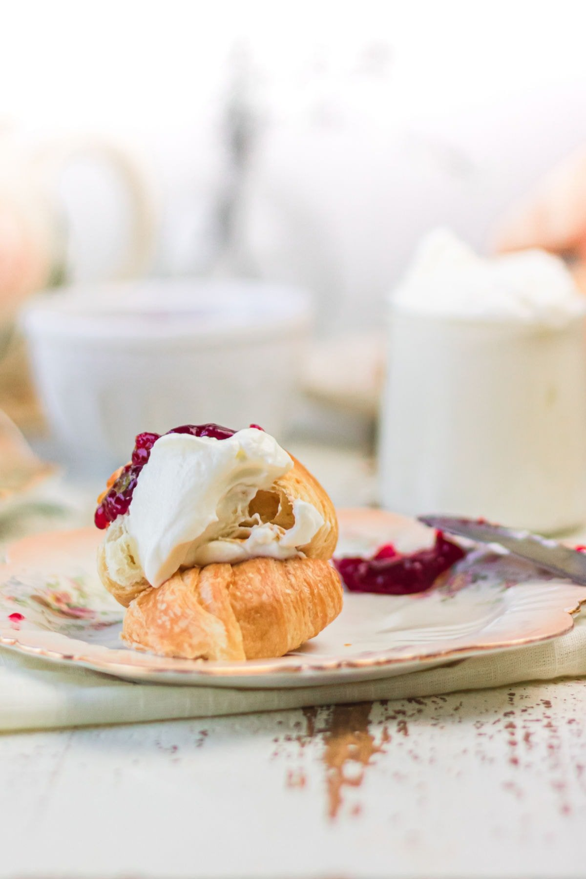 A croissant with jam and Devonshire cream spread on it.