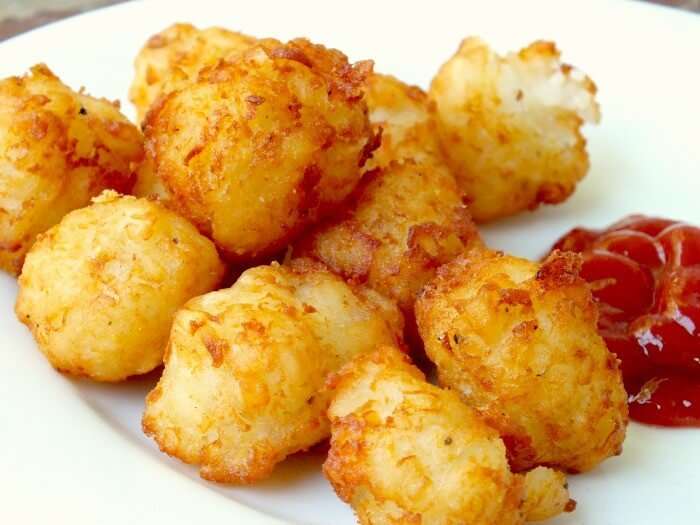 homemade tater tots on a white plate with catsup on the side.