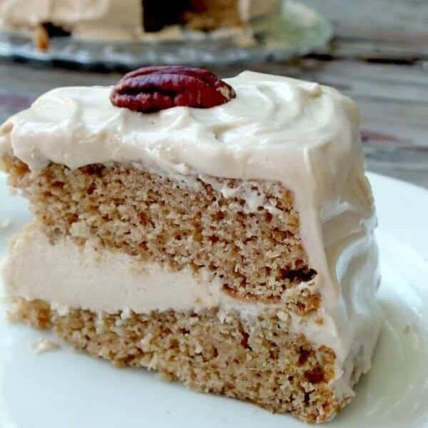 Slice of spice cake with maple cream cheese butter cream between the layers