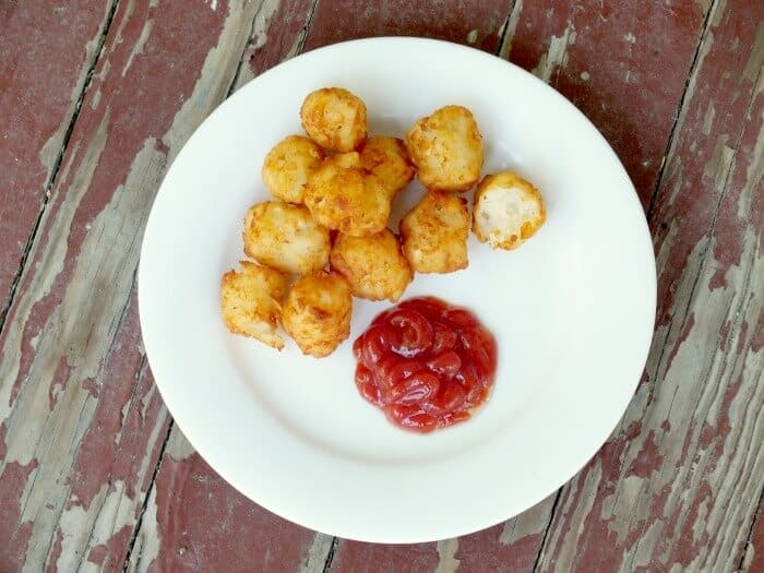 A pile of homemade tater tots on plate with a puddle of catsup next to it.