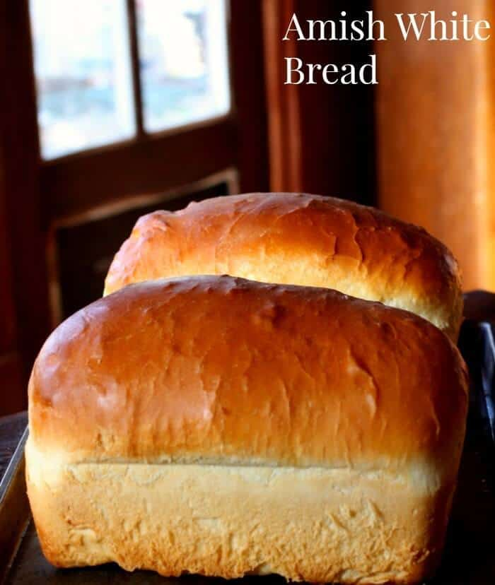 Two gorgeous loaves of golden Amish White Bread on a table - this recipe is SO easy!