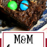 Brownies with M&Ms in the top on a blue and white plate.
