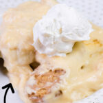 Side view of a scoop of banana pudding with whipped cream on top.