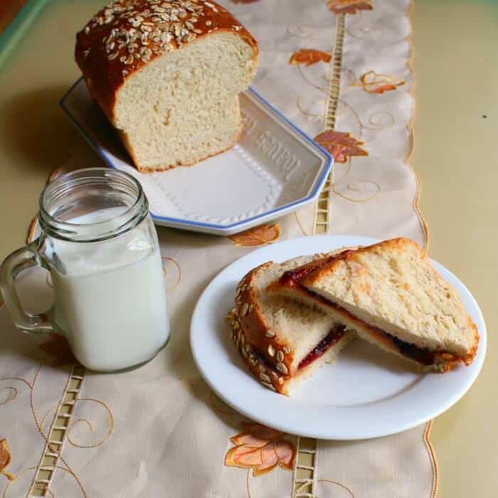 sandwich with a glass of milk - cut loaf of oatmeal bread is nearby.