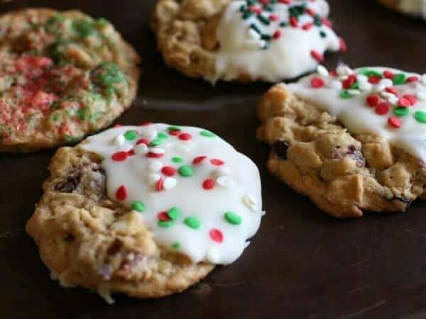 Four cranberry white chocolate oatmeal cookies dipped in white chocolate and sprinkled with red and green sprinkles