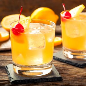 Closeup of two whiskey cocktails garnished with cherries.
